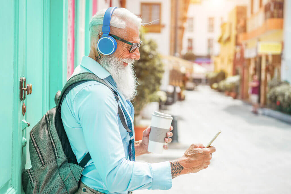 Trendy senior man using music smartphone app and drinking coffee in downtown center - Mature fashion male having fun with new trends technology.